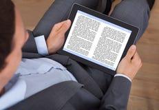 Ebook чтения бизнесмена в офисе Стоковая Фотография RF