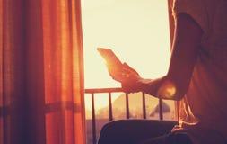 EBook чтения женщины на спальне восхода солнца в восходе солнца утра Стоковая Фотография