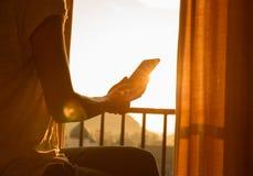 EBook чтения женщины на спальне восхода солнца в восходе солнца утра Стоковые Фото