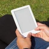Ebook чтения женщины на траве Стоковое фото RF