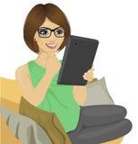 EBook чтения молодой женщины на софе Стоковое Изображение RF