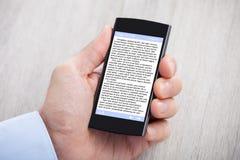 显示在智能手机的商人的手eBook 库存图片