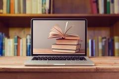 EBook arkivbegrepp med bärbar datordatoren och bunten av böcker Fotografering för Bildbyråer