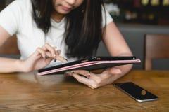 Ebook asiático da leitura da universitária do sorriso feliz com tabuleta digital foto de stock royalty free