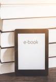 EBook avläsare på en bunt av böcker royaltyfria foton
