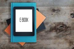 EBook avläsare på en bunt av böcker på lantligt trätabellbegrepp royaltyfria foton