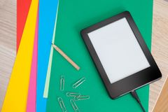 Ebook charging on colors papers with pencil and clips stock images