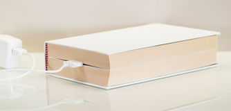 Ebook concept, battery charger. Paper traditional white charging batteries Royalty Free Stock Photos