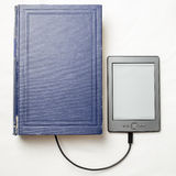 EBook connected to the old thick blue book with a cable. Top view on eBook connected to the old thick blue book with a cable, and download information from there Royalty Free Stock Image