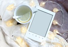 Ebook, cup and electric garland on textile background. Ebook, cup and electric garland on textile background with free copy space stock image
