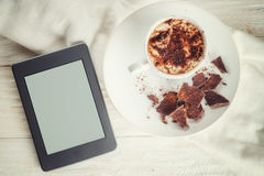 Ebook and a cup of hot cocoa royalty free stock photography
