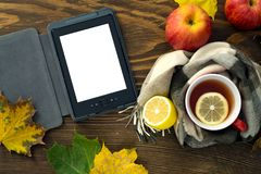 EBook and a cup of hot tea with a lemon wrapped in a scarf on a wooden table. A cup of hot tea with lemon, wrapped in a scarf, an e-book with a white screen for Stock Photos