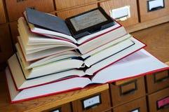 EBook czytelnik na górze sterty książki w bibliotece Obrazy Royalty Free