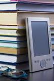 EBook czytelnik na górze sterty książki w bibliotece Zdjęcia Royalty Free