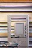 EBook czytelnik na górze sterty książki w bibliotece Zdjęcie Royalty Free