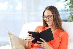 Ebook da leitura da mulher com vidros imagem de stock