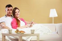 Ebook da leitura dos pares que relaxa em casa no sofá Imagens de Stock Royalty Free