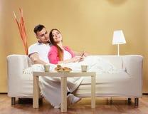 Ebook da leitura dos pares que relaxa em casa no sofá Fotos de Stock