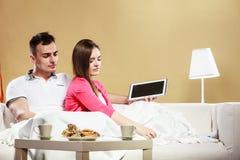 Ebook da leitura dos pares que relaxa em casa no sofá Fotografia de Stock Royalty Free