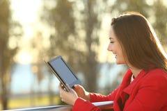 Ebook de la lectura de la mujer en la puesta del sol Fotos de archivo libres de regalías