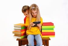 EBook du relevé de garçon et de fille entouré par des livres Images stock