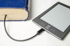 EBook förband till den gamla tjocka blåa boken med en kabel Fotografering för Bildbyråer