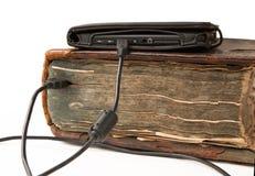 Ebook kabel förbinds med den gamla antika boken arkivbilder