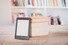 EBook-Leser auf einem Stapel Büchern lizenzfreies stockbild