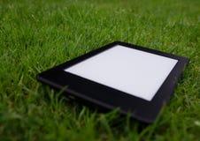 Ebook-Leser, der auf nassem Gras liegt Stockbild