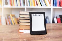 EBook-Leser und großer Stapel von Büchern stockfoto