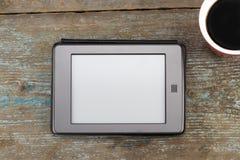EBook-Leser und Kaffeetasse auf Holztisch lizenzfreie stockfotos