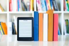Ebook-Leser und Papierbücher auf Bücherregalhintergrund stockbild