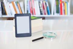 Ebook-Leser und Vergrößerungslinse auf Bücherregalhintergrund lizenzfreies stockbild