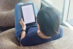 EBook Lesung der jungen Frau auf digitalem Gerät Lizenzfreies Stockfoto