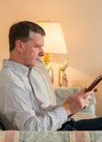 eBook Lesung des älteren Mannes auf Couch stockbilder