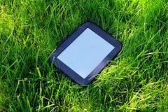 EBook noir s'étend sur l'herbe Photos stock