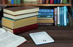 Ebook and old books on the table with bookshelf background Royalty Free Stock Photography
