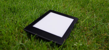 Ebook reader lying on wet grass Stock Photos