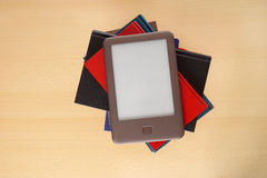 Ebook reader on pile of books Stock Photos