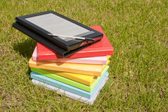 Ebook reader with a stack of books Stock Photos