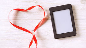 Ebook and red tape in the form of heart. Copyspace Stock Photos