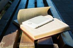 Ebook som lägger på en bok på bänken begreppsny teknik Arkivfoto