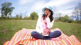 EBook sonriente atractivo de la lectura del smartphone de la mujer que habla joven metrajes