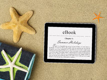 EBook tablet on beach Royalty Free Stock Images