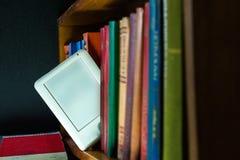 Ebook und alte Bücher auf dem Bücherregal Lizenzfreie Stockfotografie