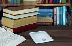 Ebook und alte Bücher auf dem Tisch mit Bücherregalhintergrund Lizenzfreie Stockfotografie
