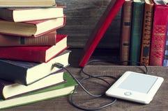 Ebook und alte Bücher auf Holztisch Stockbild