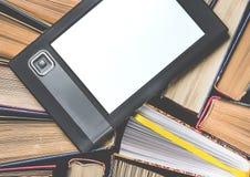 EBooken med en vit skärm ligger på de öppna mång--färgade böckerna, som ligger på en mörk bakgrund, närbild arkivbilder