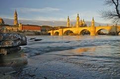 Ebro River flöde med den gamla Zaragoza sikten på soluppgång arkivfoto
