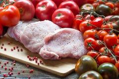 Żebruje wieprzowina kotlecików mięsną primę ciącą z pomidorami na tnącej desce Fotografia Royalty Free